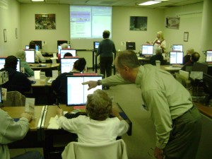 An instructor helping a student during a computer class.