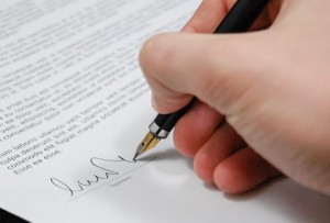 A hand holding a pen and signing a document